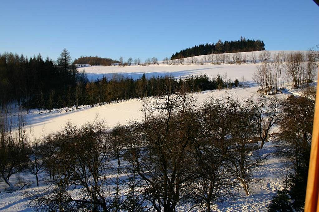 Zimní pohled z chalupy do údolí